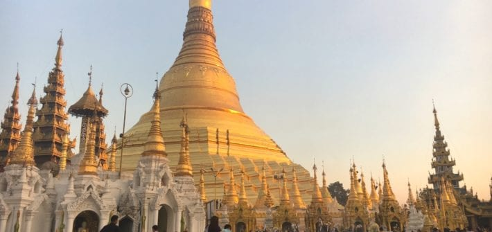 Shwedagon Pagoda at sunset with Buddhists Praying