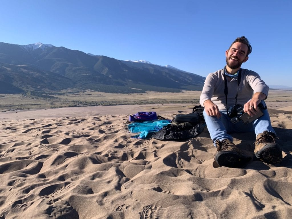 Jesse sitting on top of a dune